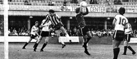 Hereford's Tommy Hughes cuts out a cross aimed at Peter Houghton